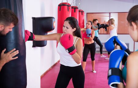 Active young female is doing exercises with punching bag in sporty gym. 写真素材