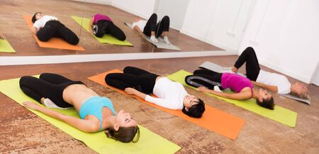 Girls perform exercises on yoga, lying on mat in the gym