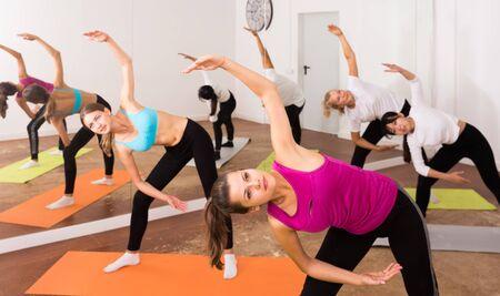 Flexible girls practice yoga in in fitness center