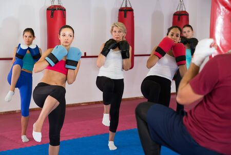 Group of smiling female are doing kick with instructor in sporty gym 写真素材