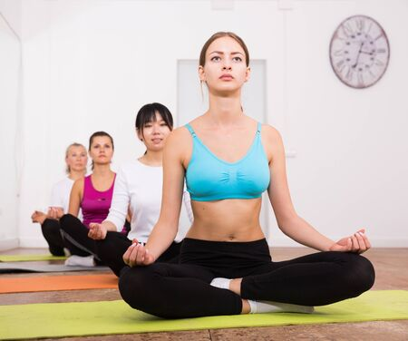 Group of young women training yoga positions in modern yoga studio
