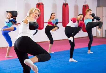 Portrait of active mature female who is training box exercises with group in sporty gym