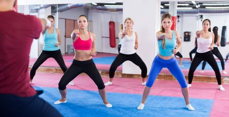 Group active women are boxing with coach in sporty gym 写真素材