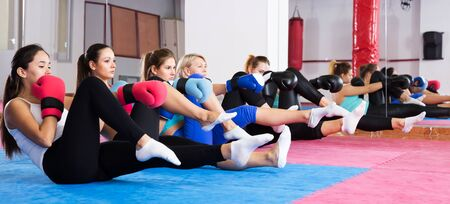 Group of women are doing box exercise sitting on the floor in gym