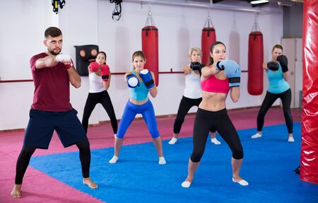 Group adult women are boxing with coach in sporty gym