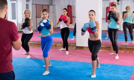 Group positive women are boxing with coach in sporty gym