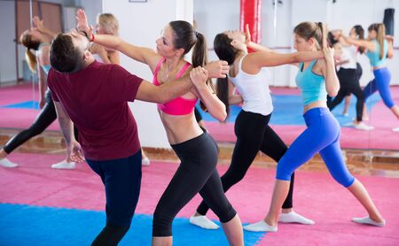 Group women are doing self-defence-karate moves with trainer in sporty gym