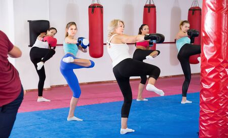 Group of female are boxing and doing kick with instructor in sporty gym