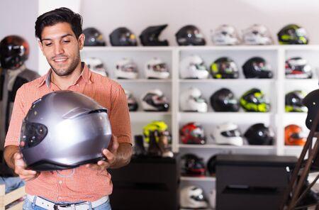 Joyful man is choosing new helmet for motorbike in the store Фото со стока