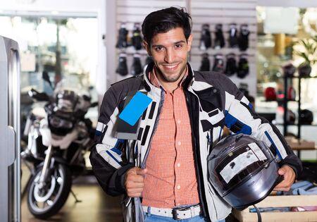 Portrait of nice man in moto jacket who is choosing new helmet for motorbike in the store