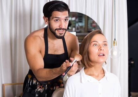 Professional makeup artist applying cosmetics for female indoors Stock fotó