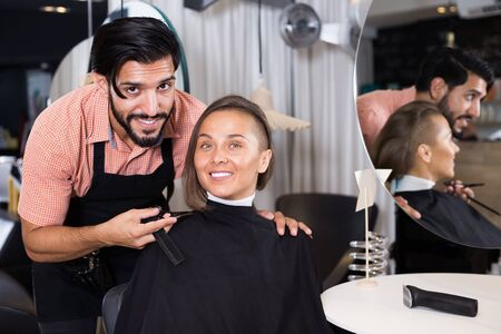 Portrait of positive man hairdresser and woman client in salon