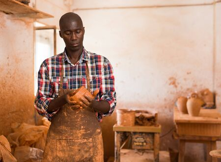 Young male potter engaged in creating ceramics in pottery studio
