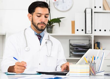Spanish man doctor is working with documents behind laptop in his office.