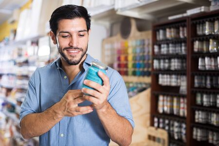 Smiling man choosing materials for home renovation in paint store Stock fotó