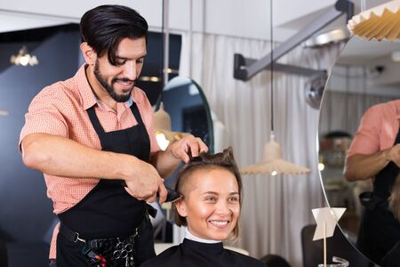Positive sexy adult hairdresser working with hair clipper with woman Фото со стока