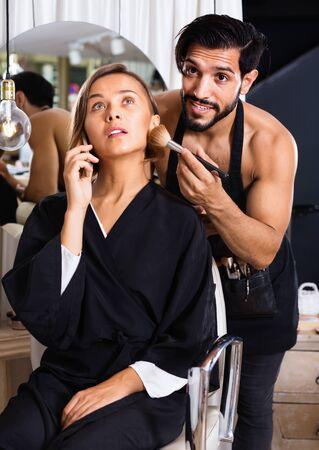 Smiling cheerful positive man makeup artist applying cosmetics for woman talking phone Stock fotó