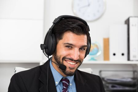 Smiling man dispatcher is speaking with client on his work place. 版權商用圖片
