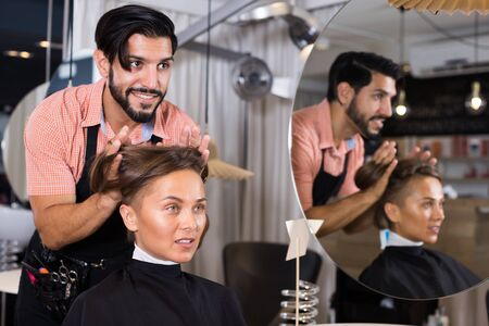 positive man hairdresser making hairstyle for woman in salon Фото со стока