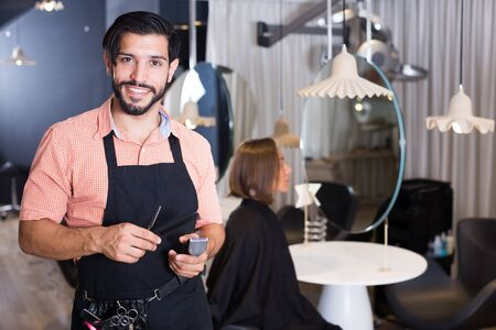 adult professional male hairdresser with visitor woman indoors