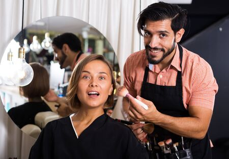Cheerful male makeup artist in salon applying cosmetics for woman Stock fotó