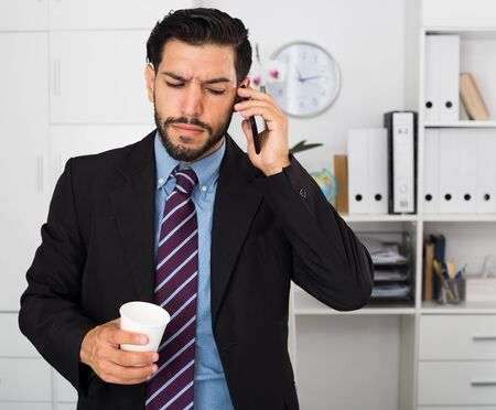Adult man is serious talking phone in his work place.