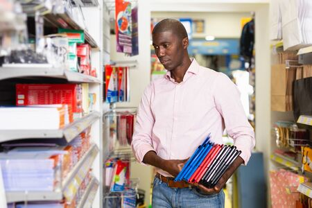 Portrait of positive African man choosing office supplies at stationery store