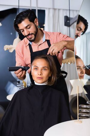 Portrait of  cheerful positive smiling man hairdresser cutting womans hair in salon
