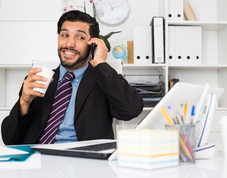 Smiling man is talking phone with his partner in office.