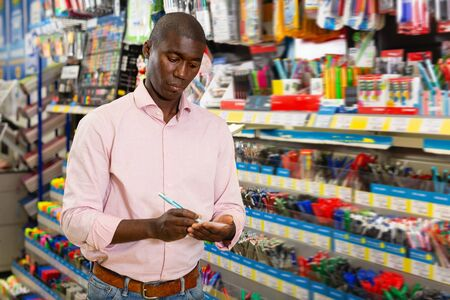 Glad African man choosing pens and pencils in office supply shop Archivio Fotografico