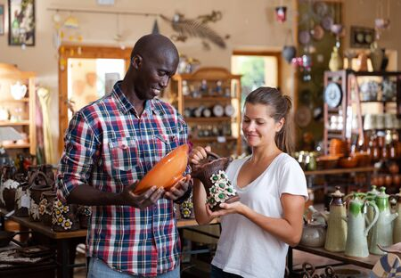 African American man and European woman visiting pottery shop