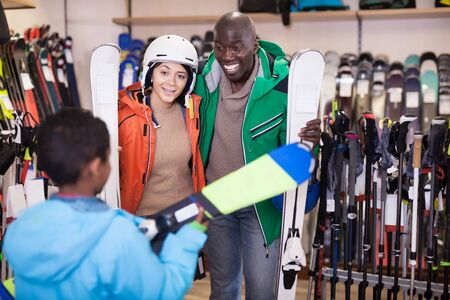 Cheerful family of young skiers choosing modern skis for preteen son in the store of sports equipment. Focus on both persons