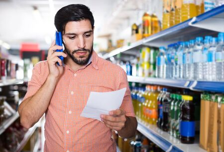 happy italian man is choosing water using note list and a call to his wife in supermarket.