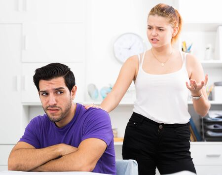 Upset young man sitting at home table with disgruntled woman behind