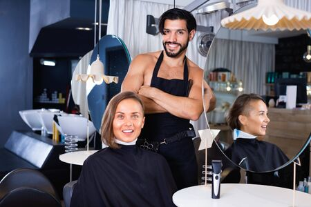 Cheerful positive  male professional with female talking about hairstyle