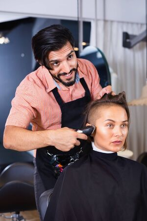 Portrait of happy smiling man hairdresser cutting womans hair in salon
