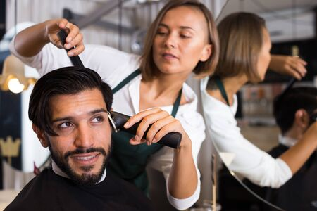 female professional shaving cheerful males hair in hairdressing salon