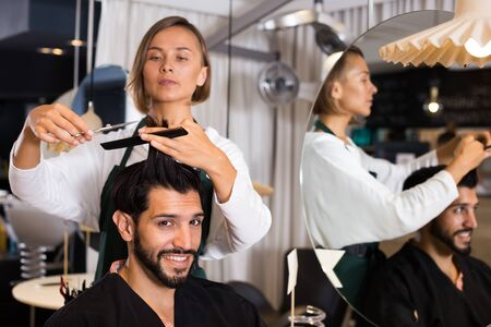 adult hairdresser working with scissors and comb with smiling man Фото со стока