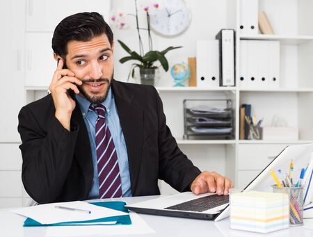 Adult man is surprised while talking phone with his partner in office. Foto de archivo
