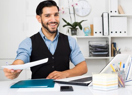 Excited male is talking about successful contract in office.
