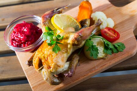Image of baked in oven game dish with cranberry sauce and grilled vegetables on wooden board
