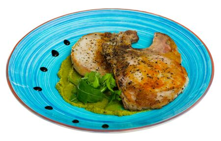 Delicious fried pork loin with green vegetable puree decorated with fresh leaves of arugula. Isolated over white background