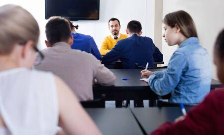 Insegnante serio che monitora il lavoro degli studenti durante la prova d'esame in classe