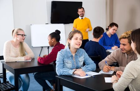 Friendly classmates working in groups to complete task during class
