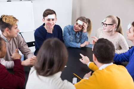 happy russian classmates having round of guess-who game during class
