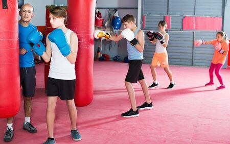 Teenage boy sportsman at boxing workout on punching bag with coach