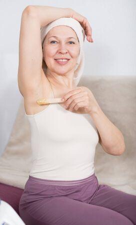 Senior woman starting body hair removal at home 版權商用圖片