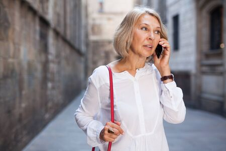 Adult female is talking by phone with friend on the street outdoor Stok Fotoğraf
