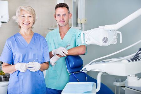 Two professional confident dentists posing near dental chair in a clinic. Focus on man