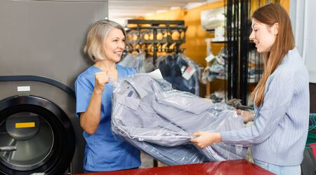 Glad cheerful female client receiving her clean clothes at dry-cleaning salon